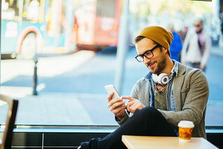 How Broadcast Media Drives Consumer Engagement - Man Texting in a Coffee Shop