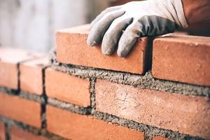 Close up of gloved hand laying bricks and mortar